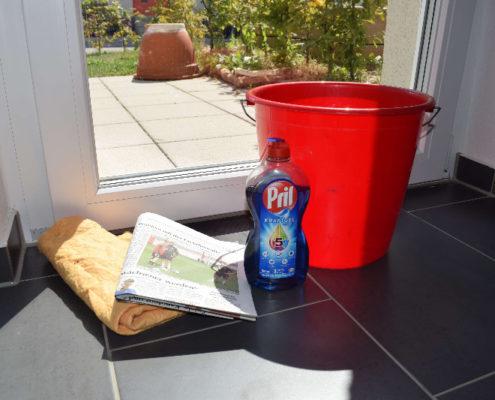 Fenster putzen mit Zeitung, Spüli, Eimer und Lappen