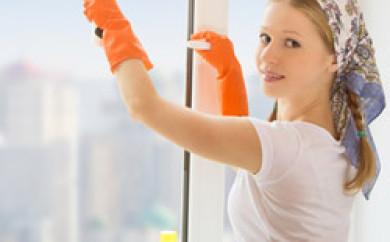Junge Frau beim Fenster putzen